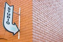 Sinal velho do estúdio da seta do vintage que aponta em uma parede de tijolo urbana fotos de stock