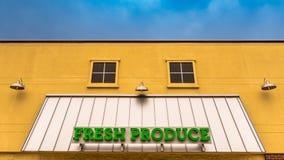 Sinal verde-claro dos produtos frescos em uma parte dianteira amarela da loja fotografia de stock