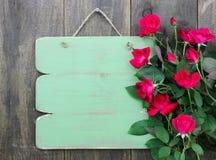 Sinal verde vazio afligido com beira da flor das rosas vermelhas que penduram na porta de madeira rústica imagem de stock
