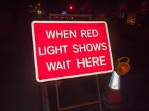 sinal vermelho da construção na estrada da noite quando as mostras da luz vermelha o esperarem fotos de stock royalty free