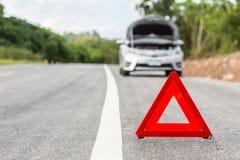 Sinal vermelho da parada de emergência e carro de prata quebrado Imagens de Stock