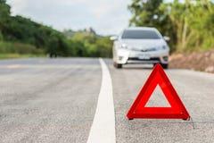 Sinal vermelho da parada de emergência e carro de prata quebrado Imagem de Stock