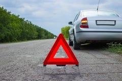 Sinal vermelho da parada de emergência e carro de prata quebrado na estrada Fotos de Stock Royalty Free