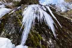 Sincelos afiados que penduram de uma formação de rocha em um vale da montanha em Romênia Fotografia de Stock Royalty Free