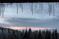 Sincelos do inverno em um quadro de janela com um Mountain View imagens de stock royalty free