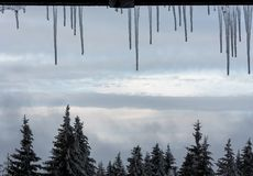 Sincelos do inverno em um quadro de janela com um Mountain View fotos de stock