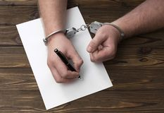 A sincere confession. statement. The hands of the criminal in handcuffs write with a pen on paper. A sincere confession. request. statement Royalty Free Stock Photo