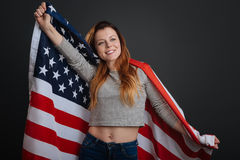 Sincere inspiring woman feeling patriotic. American vibes. Stunning magnetic sweet girl posing with a flag while working on a photoshoot and standing isolated on Royalty Free Stock Images