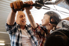 Sincere inventive family enjoying their time in garage. We gonna ride it soon. Charming hilarious nice father entertaining his child by giving her a tour around Royalty Free Stock Photo