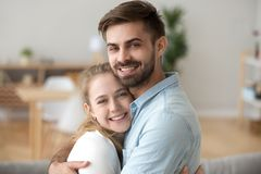 Pretty millennial just a married couple embracing indoors. Sincere just a married couple in love hugging. Head shot portrait husband and wife embracing spend royalty free stock photo