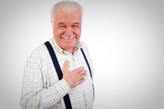 Sincere senior man with his hand on his heart. Looking at the camera with a warm friendly smile, upper body studio portrait on grey with copyspace Royalty Free Stock Photo