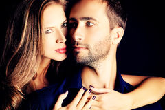 Sincerity. Portrait of a beautiful young couple in love posing at studio over dark background royalty free stock image