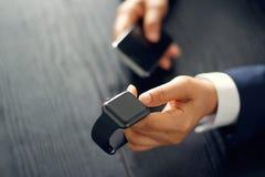 Sincronização do homem de negócios do close up, pares ou smartwatch do fósforo imagem de stock