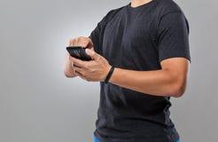 Sincronização do telefone celular do uso do homem com perseguidor da atividade Foto de Stock Royalty Free