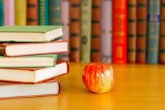 Sind auf dem Tisch Stapel von Büchern und von Apfel stockfotografie