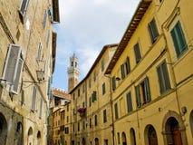 Sinea古色古香的街道与Mangia塔的在背景中。锡耶纳,意大利 免版税库存图片
