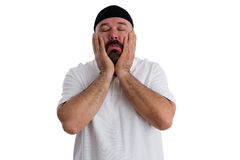 Sinful man seeking absolution. Praying to God with his hands to his cheeks, eyes closed and a devout expression as he seeks forgiveness, isolated on white Royalty Free Stock Photos