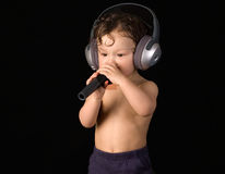 Sing baby. Sing baby with headphone and microphone,isolated on a black background royalty free stock image