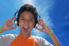 Sing Out Loud. A boy singing while listening to music on his headphone Royalty Free Stock Image