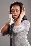 Sing song african american girl recording studio. Beautiful young black girl wearing headphones and singing into microphone in recording studio Stock Photography