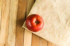 Singal jabłko na kąt macie z drewnianą tło teksturą Obraz Royalty Free