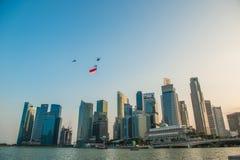 Singapore 50 år repetitionhelikopter för nationell dag som hänger den Singapore flaggan som flyger över staden Fotografering för Bildbyråer