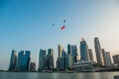Singapore 50 år repetitionhelikopter för nationell dag som hänger den Singapore flaggan som flyger över staden royaltyfria foton