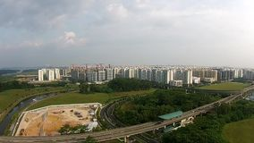 Singapore - Aerial view of light rail train entering and leaving station stock video
