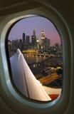 Singapore through Aircraft Window. View of central Singapore city through an aircraft window at night Stock Photos