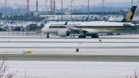 Singapore Airlines acepilla en pista en el aeropuerto de Munich, Alemania, invierno con nieve metrajes