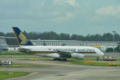 Singapore Airlines Airbus 380 super jumbo being towed across taxi-way at Changi Airport Royalty Free Stock Photos