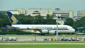 Singapore Airlines Airbus 380 super jumbo being towed across taxi-way at Changi Airport. SINGAPORE - JANUARY 10: Singapore Airlines Airbus 380 super jumbo being Royalty Free Stock Image