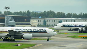 Singapore Airlines Boeing 777-200ER passing a fellow Airbus 380 super jumbo at Changi Airport. SINGAPORE - JANUARY 10: Singapore Airlines Boeing 777-200ER Royalty Free Stock Images