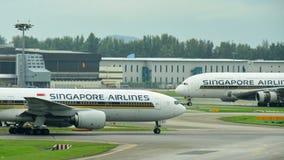 Singapore Airlines Boeing 777-200ER que pasa un jumbo estupendo de Airbus 380 compañeros en el aeropuerto de Changi Imágenes de archivo libres de regalías