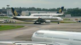 Singapore Airlines Boeing 777-200ER que passa um jumbo super de Airbus 380 companheiros no aeroporto de Changi Fotos de Stock Royalty Free
