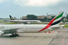 Singapore Airlines Boeing 777-200 passing an Emirates Boeing 777-300ER Stock Image