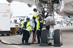 Singapore Airshow 2014. SINGAPORE - FEBRUARY 11: Ground crew connecting cables to Airbus A350 XWB prototype 003 at Singapore Airshow, Changi Exhibition Centre in royalty free stock photo