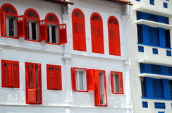 Singapore: Amoy Street Houses. Handsome white early 20th century houses with deep red and blue louvered shutters on Amoy Street in the Chinatown district of Royalty Free Stock Image