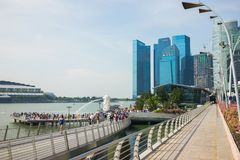 Singapore - Apr 30, 2016: Marina Bay with walking bridge, crowded people and high buildings on background.  Stock Photo