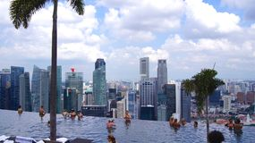 SINGAPORE - APR 1st, 2015: Rooftop infinity pool at the Marina Bay Sands Skypark, with people relaxing to the. Breathtaking views Stock Images