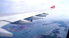 SINGAPORE - APR 1st, 2015: View from the cloud, landscape, islands and airplane wing - see through airplane window. Before landing at Singapore International Royalty Free Stock Photo