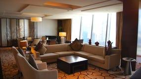 SINGAPORE - APRIL 2nd 2015: Härlig vardagsruminre med sikt i ett lyxigt hotellrum av Marina Bay Sands Resort royaltyfria foton