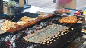 SINGAPORE - APRIL 3rd, 2015: Läckra smakliga steknålar av den fega kocken över varma kol i mat för gata för Singapore ` s Satay Arkivbilder