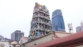 SINGAPORE - APRIL 3rd 2015: Sri Mariamman den hinduiska templet i kineskvarter med skyskrapan i bakgrunden Arkivbild