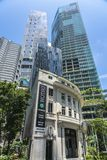 Old in front of new and modern tall buildings royalty free stock photo