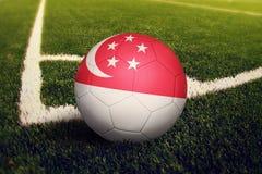 Singapore boll p? positionen f?r h?rnspark, bakgrund f?r fotbollf?lt Nationellt fotbolltema p? gr?nt gr?s royaltyfri fotografi