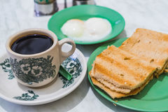 Singapore Breakfast Kaya Toast, Coffee bread and Half-boiled egg. Singapore Breakfast called Kaya Toast, Coffee bread and Half-boiled eggs, Chinese coffee in Royalty Free Stock Photography