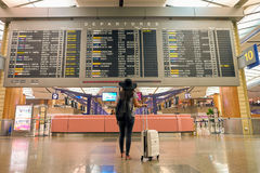 Singapore Changi Airport Terminal 2 departure hall. SINGAPORE - CIRCA AUGUST, 2016: woman stand back side and look at timetable departure board in Singapore stock photography