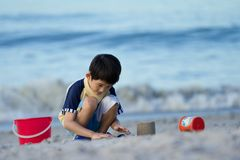 Young asian boy plays at the beach royalty free stock image