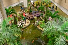 SINGAPORE - CIRCA MARCH, 23, 2018: Above view of people walking in a small garden with plants inside of Singapore Changi. Airport. Singapore Changi Airport is Stock Images